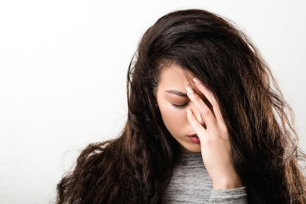 Портрет скорбящей, опечаленной эмоциональной девушки, закрывающей лицо рукой. выражение лица печальное, глаза закрыты.