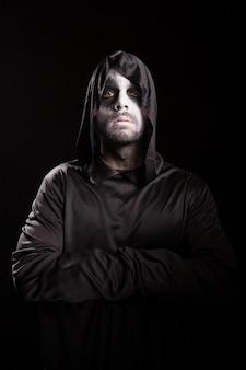 黒い背景の上に孤立した手を交差させた死神の肖像画。ハロウィーンの衣装。