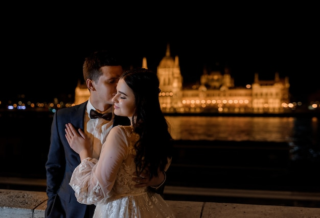 建築ヨーロッパでの結婚式の新婚旅行、夜の街の美しい景色を望む新郎新婦の肖像画