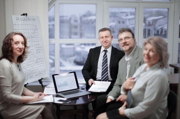 Портрет группы деловых людей, сидящих возле рабочего стола в офисе