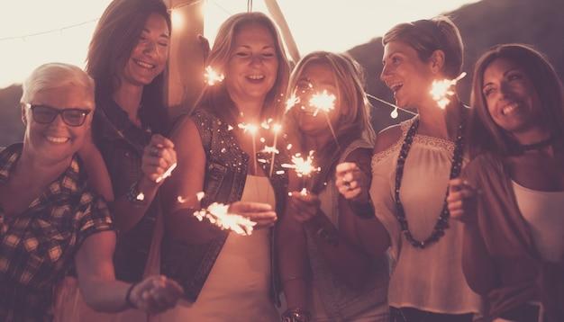 野外パーティーで線香花火で祝う女性の友人のグループの肖像画楽しんでいる友人