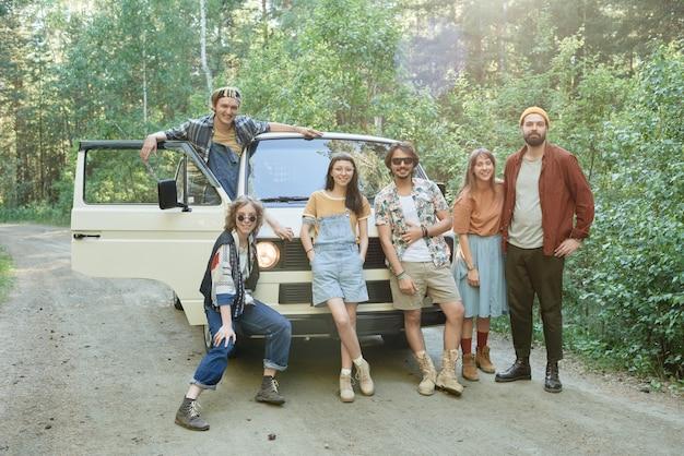 숲에 서 있는 밴 근처에서 포즈를 취한 카메라를 보며 웃고 있는 친구들의 초상화