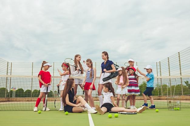 Портрет группы в составе девушки и мальчик как теннисисты держа ракетки тенниса против зеленой травы открытого суда.