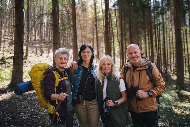 カメラを見て、自然の森の屋外でシニアハイカーのグループの肖像画。