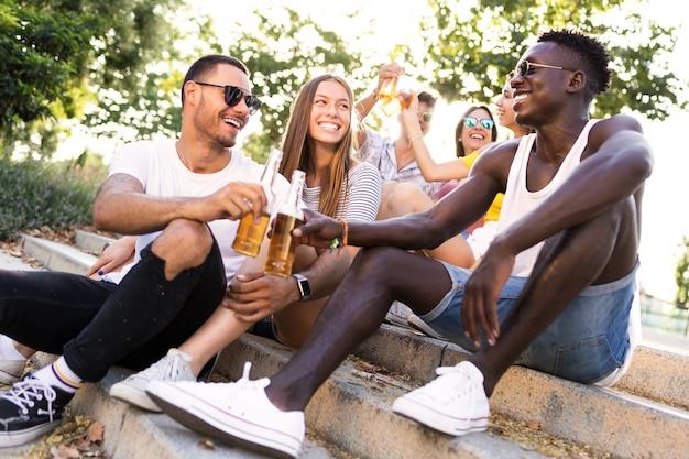 도시 지역에서 맥주와 함께 건배하는 젊은 사람들의 그룹의 초상화.