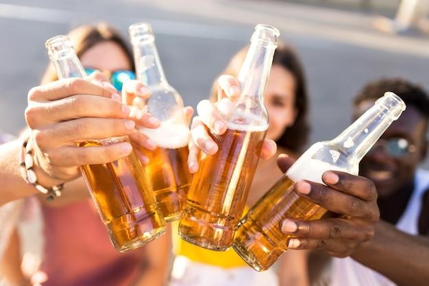 都市部でビールで乾杯する若者のグループの肖像画。