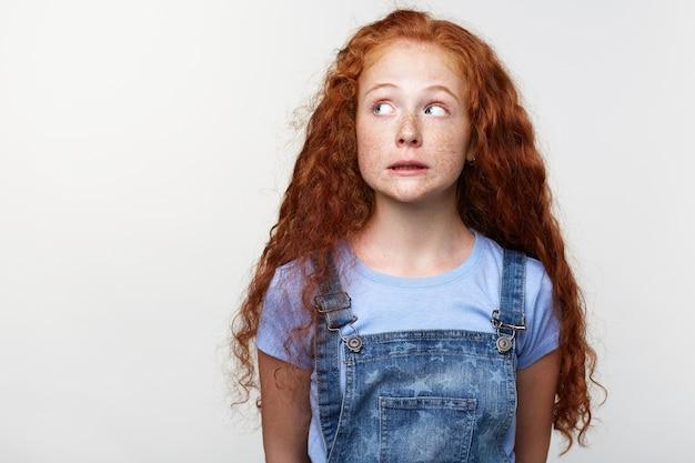 Портрет виноватой милой маленькой девочки с веснушками с рыжими волосами, которая делает вид, что не делает ничего плохого, смотрит в сторону на белом фоне с копией пространства на левой стороне.