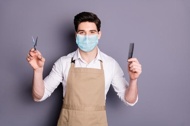 남자 이발사의 초상화는 안전 마스크를 착용하고 가위 빗을 잡고 감염 조치를 중지합니다.