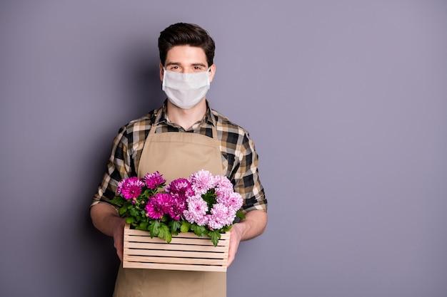 남자 정원사의 초상화는 안전 마스크를 착용하고 꽃 냄비를 멈추고 예방 조치를 취합니다.