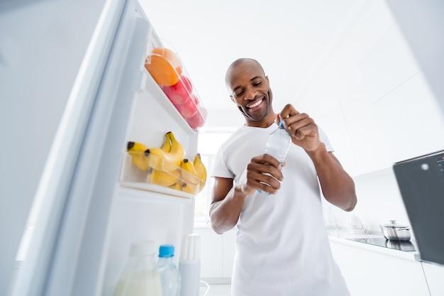 실내 주방에서 간식 건강 관리 생활 방식을 취하고 있는 냉장고를 보고 있는 남자의 초상화