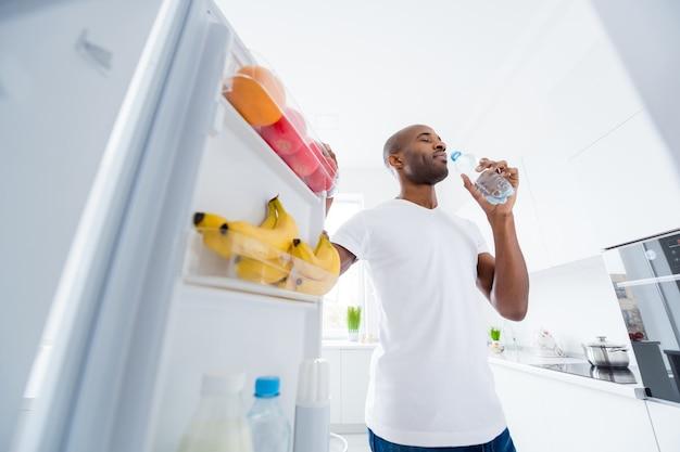 Портрет парня смотрит в холодильник, принимая закуски, режим образа жизни здравоохранения на кухне в помещении