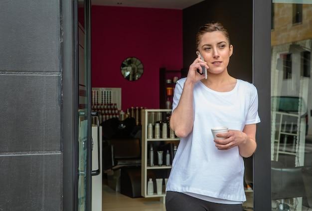 헤어 및 뷰티 살롱에서 커피를 마시며 스마트폰으로 이야기하는 미용사 여성의 초상화