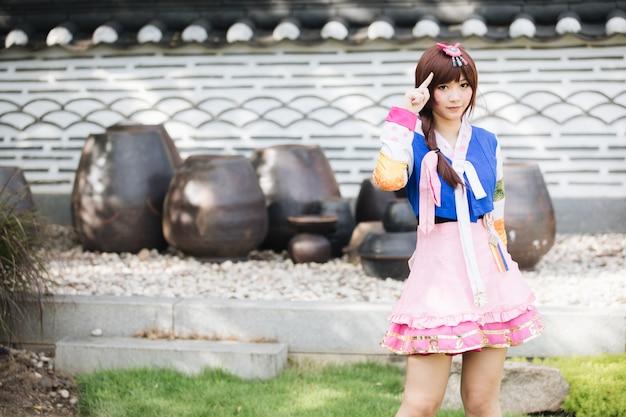 한복 의상 젊은 여자의 초상화 찾고 한국 공원에서 미소