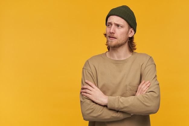 Портрет красивого взрослого мужчины со светлыми волосами и бородой. в зеленой шапке и бежевом свитере. держит руки скрещенными. наблюдая за копией слева, изолируйте желтую стену.