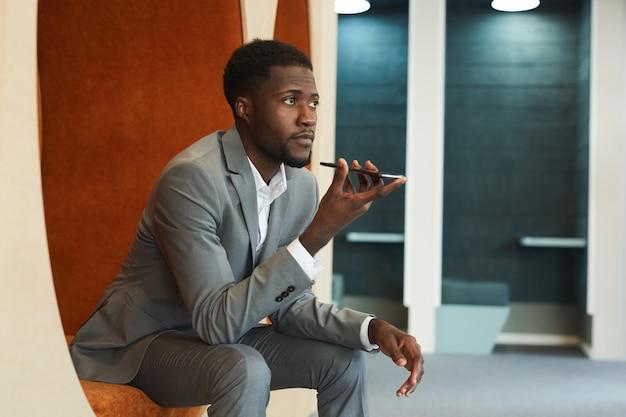 현대 사무실 또는 공동 작업 공간의 라운지 영역에 앉아있는 동안 스마트 폰을 통해 음성 메시지를 녹음하는 잘 생긴 아프리카 계 미국인 사업가의 초상화