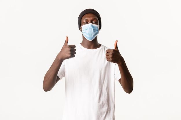 ビーニー帽と医療マスクのハンサムなアフリカ系アメリカ人の若い男の肖像画