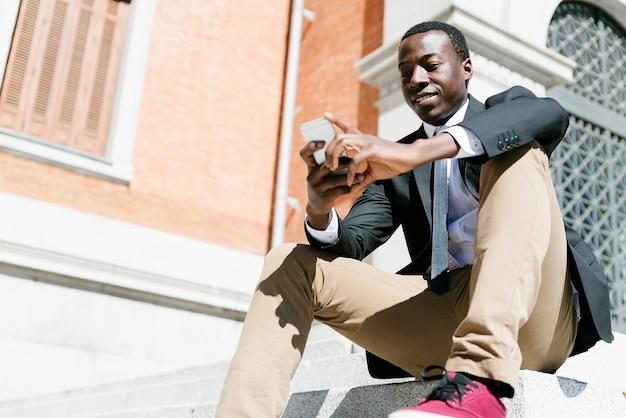 Портрет красивый африканский мужчина улыбается, когда он использует свой мобильный телефон на улице.