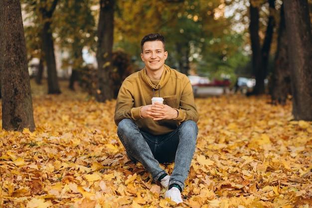 Портрет красивого и счастливого мальчика, улыбающегося и пьющего кофе в осеннем парке