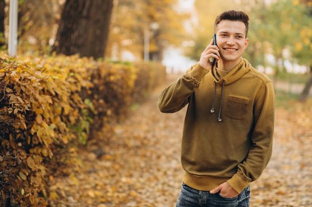 Портрет красивого и счастливого парня, улыбающегося и разговаривающего по телефону в осеннем парке
