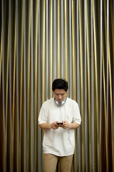 Портрет красивого азиатского мужчины, использующего смартфон и наушники на открытом воздухе
