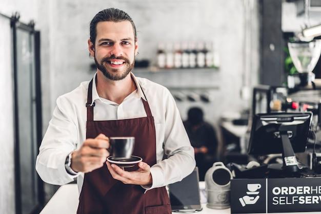 Портрет красивого бородатого бариста человек мелкого предпринимателя, улыбаясь и держа чашку кофе в кафе или кафе. мужской бариста стоит в кафе