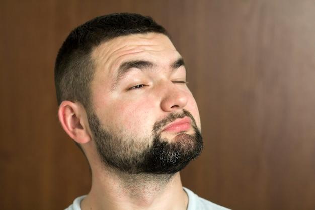 短いヘアカットとぼやけた背景に笑みを浮かべて優しい黒い目とメガネでハンサムなひげを生やした黒髪のインテリジェントな現代の若い男の肖像画。若さと自信の概念。