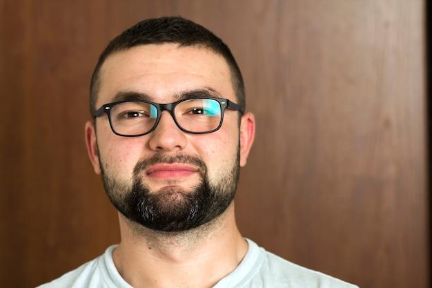 Портрет красивого бородатого черноволосого умного современного молодого человека в очках с короткой стрижкой и добрыми черными глазами, улыбающимися на размытом. концепция молодости и уверенности.