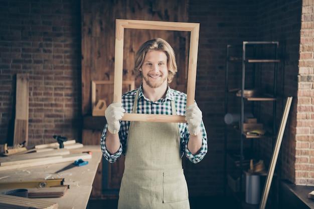彼のウッドショップでポーズをとってハンサムなひげを生やした職人の肖像画