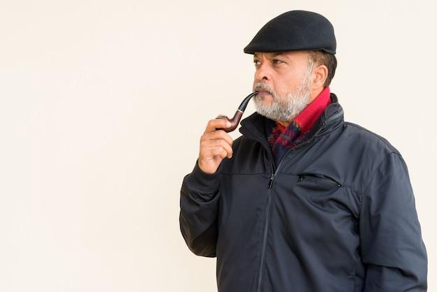 Портрет красивого бородатого индейца, курящего трубку у простой стены