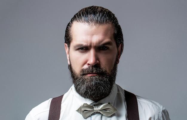 Портрет красивого бородатого мужчины в белой рубашке и галстуке-бабочке, подтяжках. крупный план джентльмена с его галстуком-бабочкой. борода человек в галстуке-бабочке и подтяжках. мужчина в рубашке поправляет свой красочный галстук.