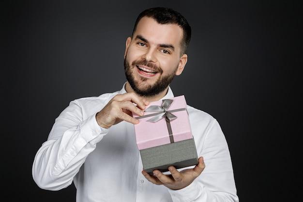 Портрет красивого бородатого мужчины в белой рубашке открывает подарочную коробку и смотрит в камеру, изолированную на черном фоне
