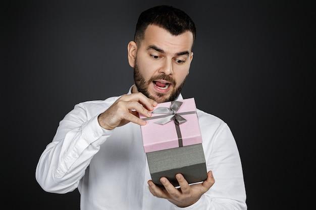 Портрет красивого бородатого мужчины в белой рубашке открывает подарочную коробку на черном фоне