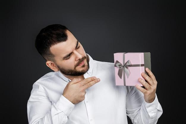 Портрет красивого бородатого мужчины в белой рубашке показывает подарочную коробку, изолированную на черном фоне