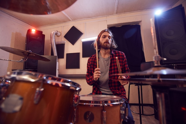 Портрет красивого бородатого мужчины, играющего на барабанах с современной музыкальной группой