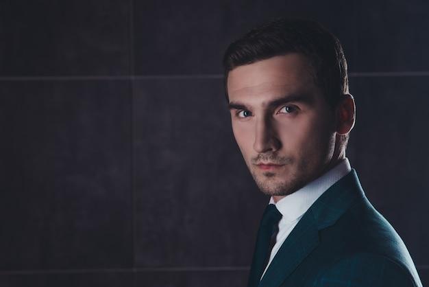 黒のスーツを着ているハンサムなひげを生やした男の肖像画