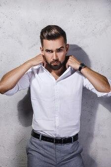 흰 셔츠를 입고 잘 생긴 수염 난된 남자의 초상화는 콘크리트 벽에 포즈입니다
