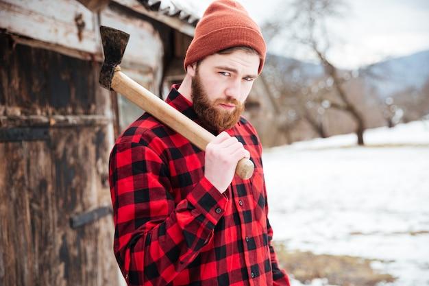 Портрет красивого бородатого мужчины с топором в деревне