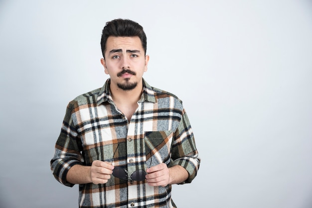 포즈와 흰 벽 위에 서있는 안경 잘 생긴 수염 된 남자의 초상화.