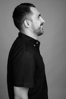 黒と白の灰色の黒いシャツを着ているハンサムなひげを生やしたペルシャ人の肖像画