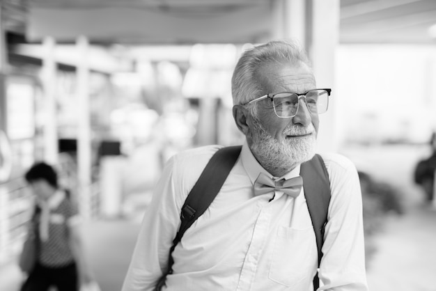 黒と白でバンコクの街を探索しながらスタイリッシュな服を着てハンサムなひげを生やしたシニア観光男性の肖像画