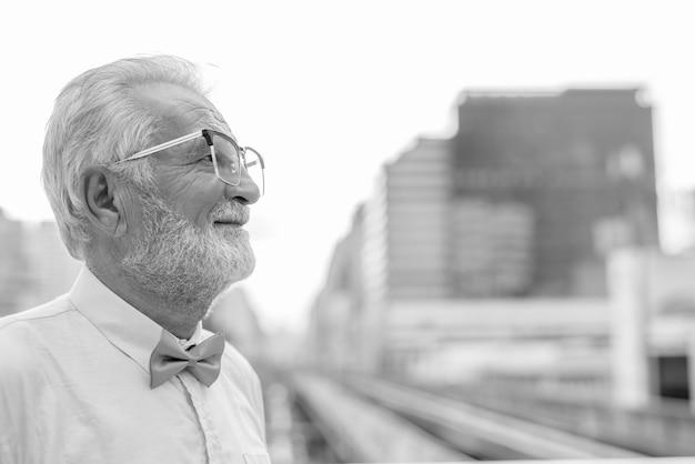 Портрет красивого бородатого старшего туриста в стильной одежде во время изучения города бангкок в черно-белом