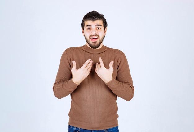 갈색 스웨터 서 고 자신을 가리키는 잘 생긴 수염 된 젊은 남자의 초상화.