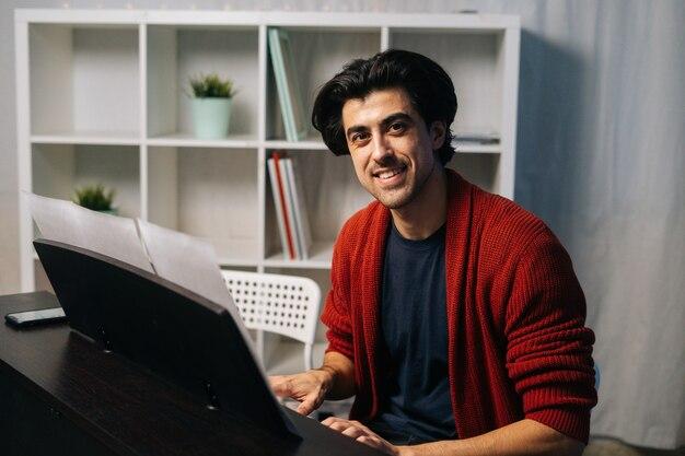 자유 시간에 거장 음악을 즐기는 피아노에 앉아 수염 난 젊은 피아니스트 남자의 초상화