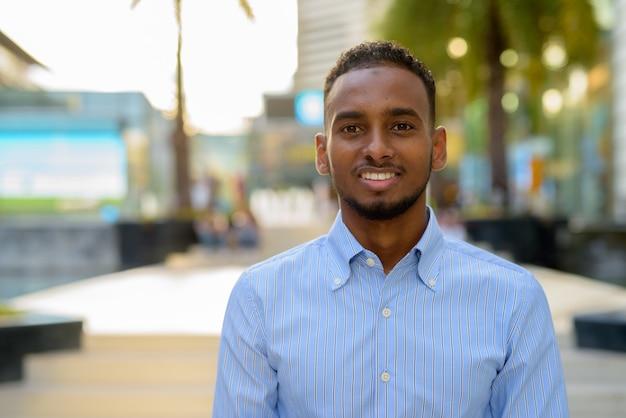 Портрет красивого черного африканского бизнесмена на открытом воздухе в городе летом, улыбаясь и глядя в камеру
