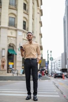 街の屋外でカジュアルな服を着て、携帯電話を使用してハンサムな黒人の若いアフリカのビジネスマンの肖像画