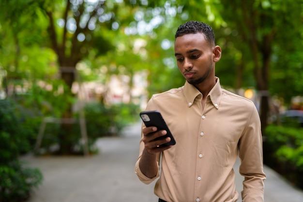 都市の屋外でカジュアルな服を着ているハンサムな黒人の若いアフリカ人実業家の肖像画
