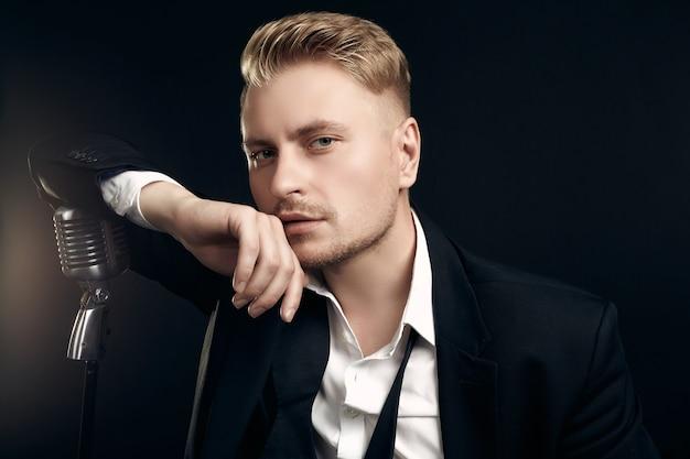 エレガントなタキシードと黒の壁にビンテージマイクでポーズをとって蝶ネクタイでハンサムな金髪の男の歌手の肖像画