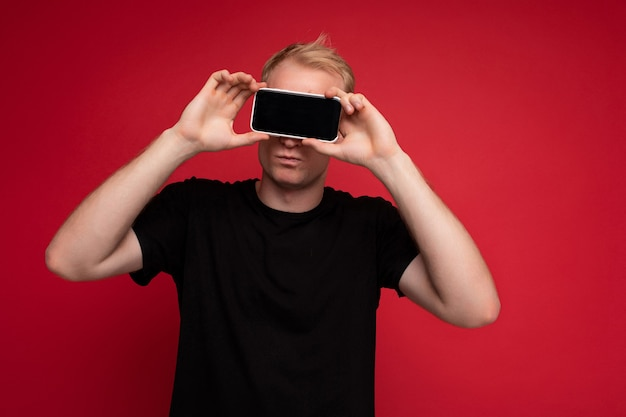 立っている黒いtシャツを着ているハンサムな金髪の若い男の肖像画