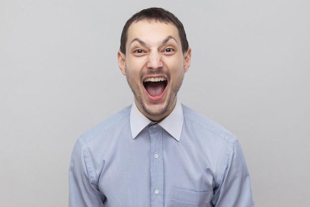 Портрет бизнесмена красивой щетины в классической голубой рубашке, стоящей с открытым ртом, крича и смотрящей в камеру. крытая студия выстрел, изолированных на сером фоне copyspace.