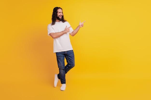 ハンサムな黒髪の男の直接指コピースペースの肖像画は黄色の背景に側面を見てください